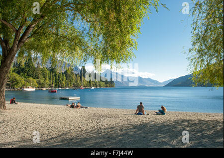 Tourists relax at the shore of Lake Wakatipu in Queenstown, New Zealand. - Stock Photo