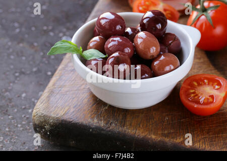 Italian food still life - olives, tomatoes, basil, prosciutto ham - Stock Photo