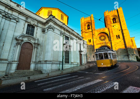 Tram in front of the Lisbon Cathedral at sunset - Stock Photo