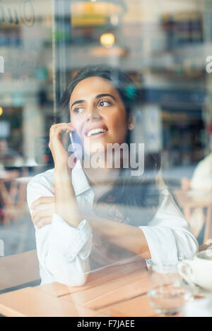 Woman talking on cell phone in coffee shop - Stock Photo