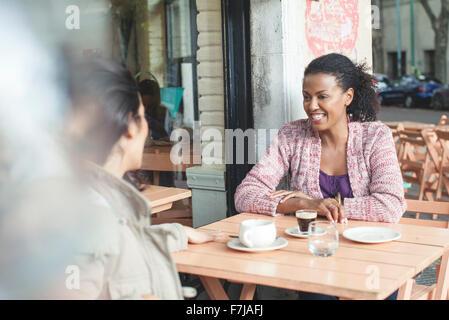 Friends talking at sidewalk cafe - Stock Photo