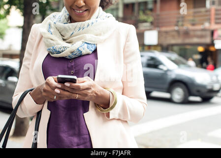 Woman text messaging on street - Stock Photo