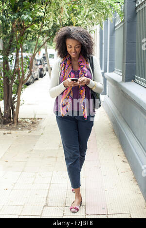Woman text messaging while walking on sidewalk - Stock Photo