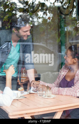 Waiter talking to customers in coffee shop - Stock Photo