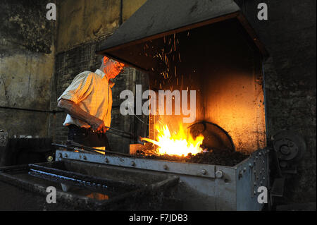 Farrier at work in his forge making horse shoes - Stock Photo
