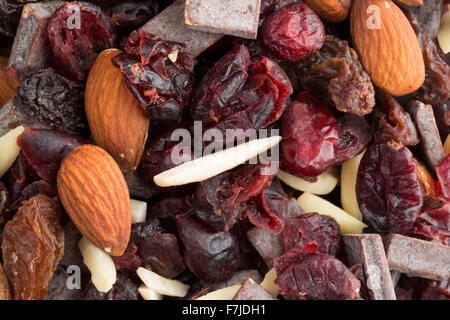 Close view of a trail mix consisting of dried cranberries, sliced almonds, raisins and chunks of chocolate - Stock Photo