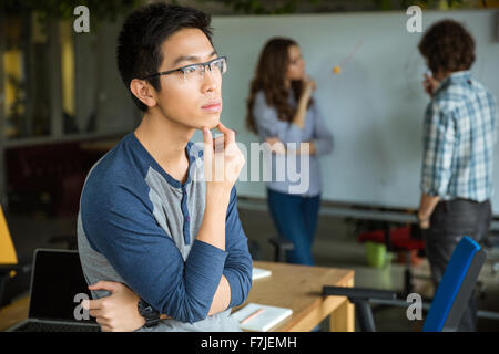 Pensive concentrated handsome young asian man in glasses thinking and working with colleagues - Stock Photo