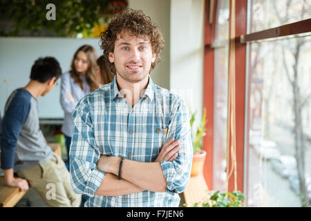 Attractive positive curly young male in checkered shirt posing in office with folded hands standing near the window - Stock Photo