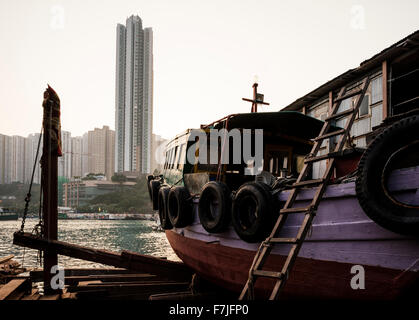 Exterior of Boat with high rise building in background, Aberdeen Harbour, Hong Kong Island, China - Stock Photo