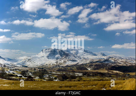 A scenic view of Cader Idris from the east with the mountain range covered in spring snow, greening fields in the - Stock Photo
