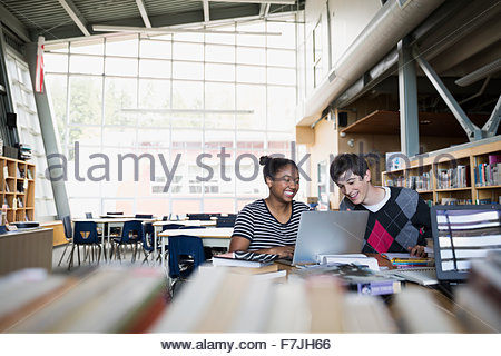 High school students studying at laptop in library - Stock Photo