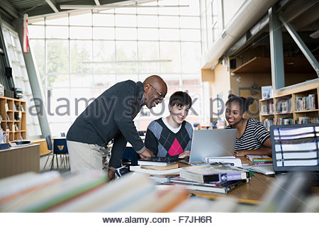 High school students and teacher using laptop library - Stock Photo