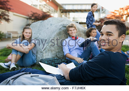 Portrait smiling high school student studying on campus - Stock Photo