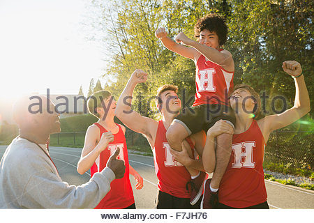 Enthusiastic high school track and field team celebrating - Stock Photo
