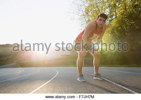 Tired high school track and field athlete - Stock Photo