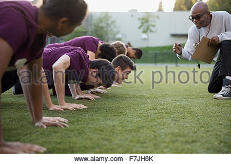Physical education teacher encouraging students doing push-ups - Stock Photo