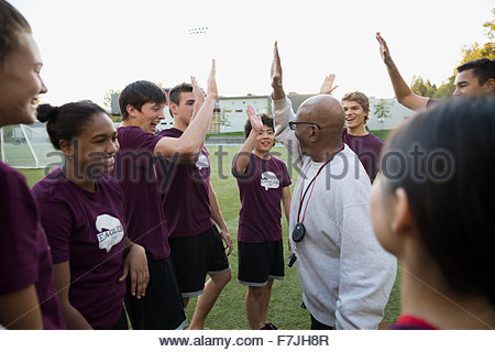 Physical education teacher high fiving high school students - Stock Photo