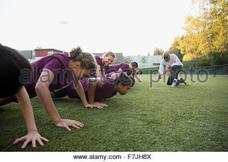 Physical education teacher encouraging students doing push-ups - Stock Photo
