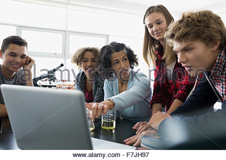 High school students and science teacher talking laptop - Stock Photo