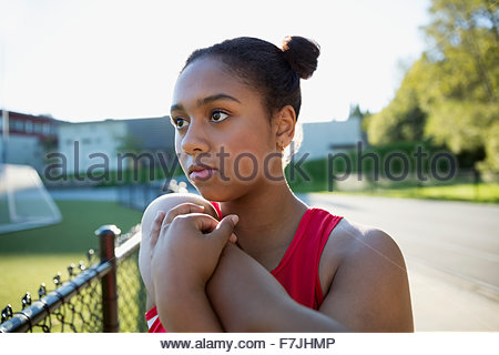 Determined high school athlete stretching arm running track - Stock Photo