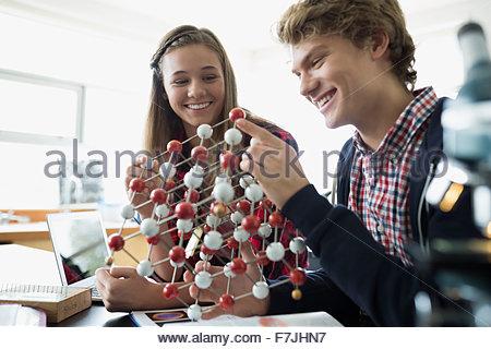 Smiling high school students examining atom model classroom - Stock Photo