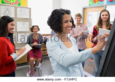 High school students watching art teacher in classroom - Stock Photo