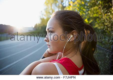 Serious high school athlete listening music running track - Stock Photo