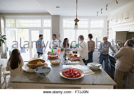 Multi-generation family socializing and eating in kitchen - Stock Photo