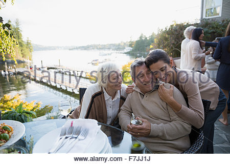 Daughter hugging senior parents on lakeside patio - Stock Photo