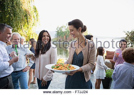 Woman serving food on lakeside patio - Stock Photo