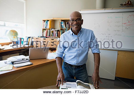 Portrait confident chemistry teacher with textbook in classroom - Stock Photo