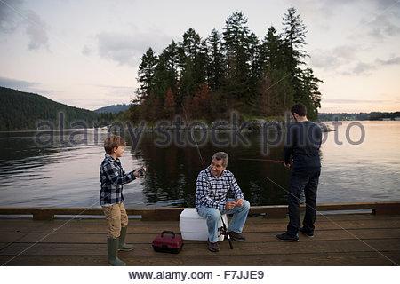 Multi-generation men fishing on lake dock - Stock Photo