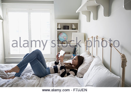 Teenage girl laying using digital tablet on bed - Stock Photo