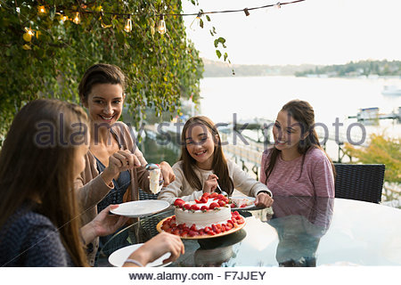 Mother serving strawberry cake to daughters lakeside patio - Stock Photo