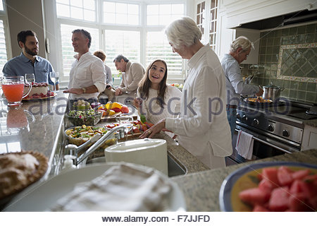 Multi-generation family cooking in kitchen - Stock Photo