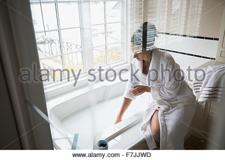 Woman in bathrobe preparing bubble bath - Stock Photo