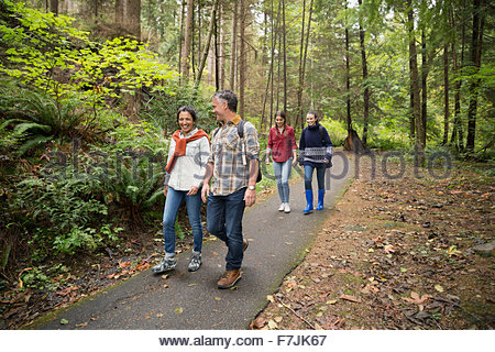 Family hiking on path in woods - Stock Photo