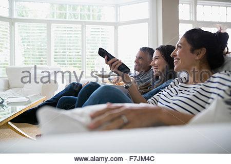 Family watching TV on living room sofa - Stock Photo