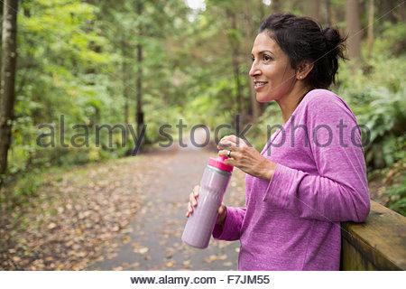 Smiling woman taking a break drinking water woods - Stock Photo