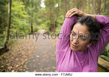 Woman stretching arms preparing for run in woods - Stock Photo
