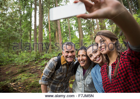Family hiking taking selfie in woods - Stock Photo