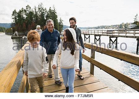 Multi-generation family walking on lake dock - Stock Photo