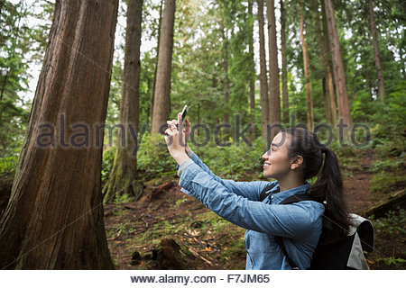 Young woman taking selfie in woods - Stock Photo