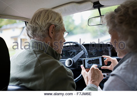 Senior couple using cell phone in car - Stock Photo