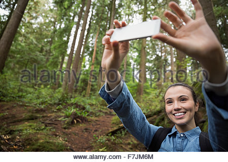 Young woman hiking taking selfie in woods - Stock Photo