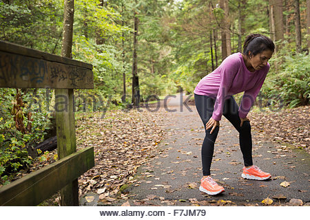 Tired woman resting hands knees after run woods - Stock Photo