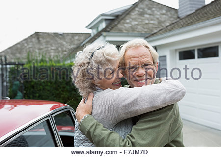 Portrait smiling senior couple hugging in driveway - Stock Photo