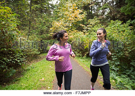 Mother and daughter jogging on path in woods - Stock Photo