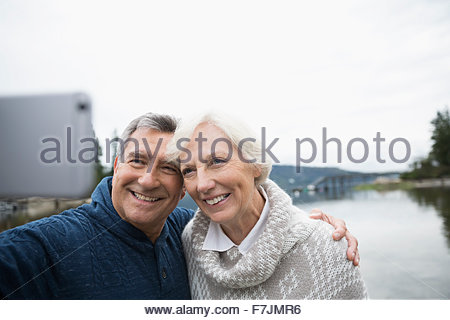 Senior couple taking selfie with lake in background - Stock Photo