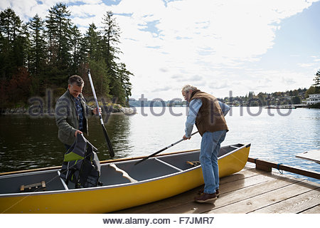 Father and son preparing canoe on lake dock - Stock Photo